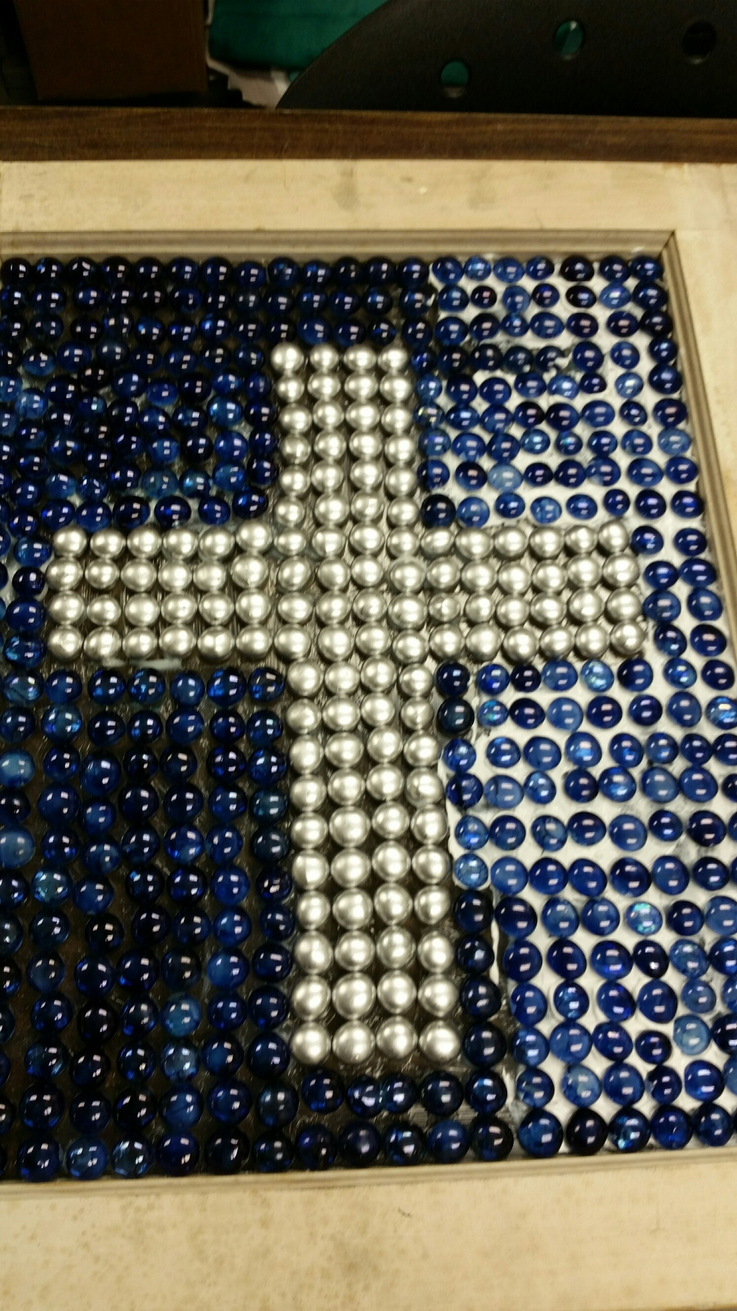 Beaded window white cross with blue background