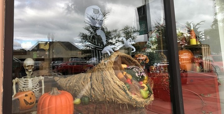 Store window, featuring fall and Halloween decorations.