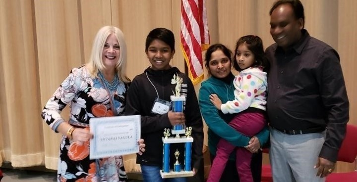 Picture of Yuvaraj (Raj) Vagula, winner of the 36th Annual Lake County Spelling Bee, his family, and Lake County ESC Superintendent Jennifer Felker