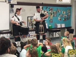 Picture of two members of the Cleveland Firefighter's Pipe & Drum surrounded by Preschool students.